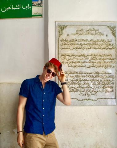 Student in front of Arabic sign in Fes